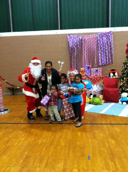 Santa and Mrs. Claus pose with a Palama family in the Palama gym.