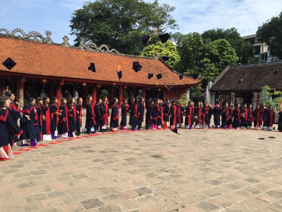 College grads in Hanoi visit a temple where they celbrate and throw their mortar boards into the clear blue sky.