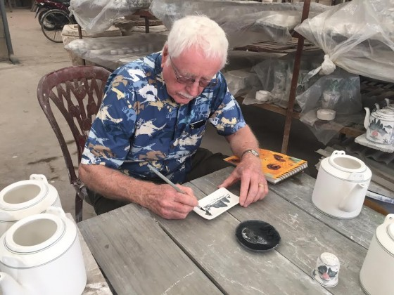 Jerry puts his marks on a clay plate.